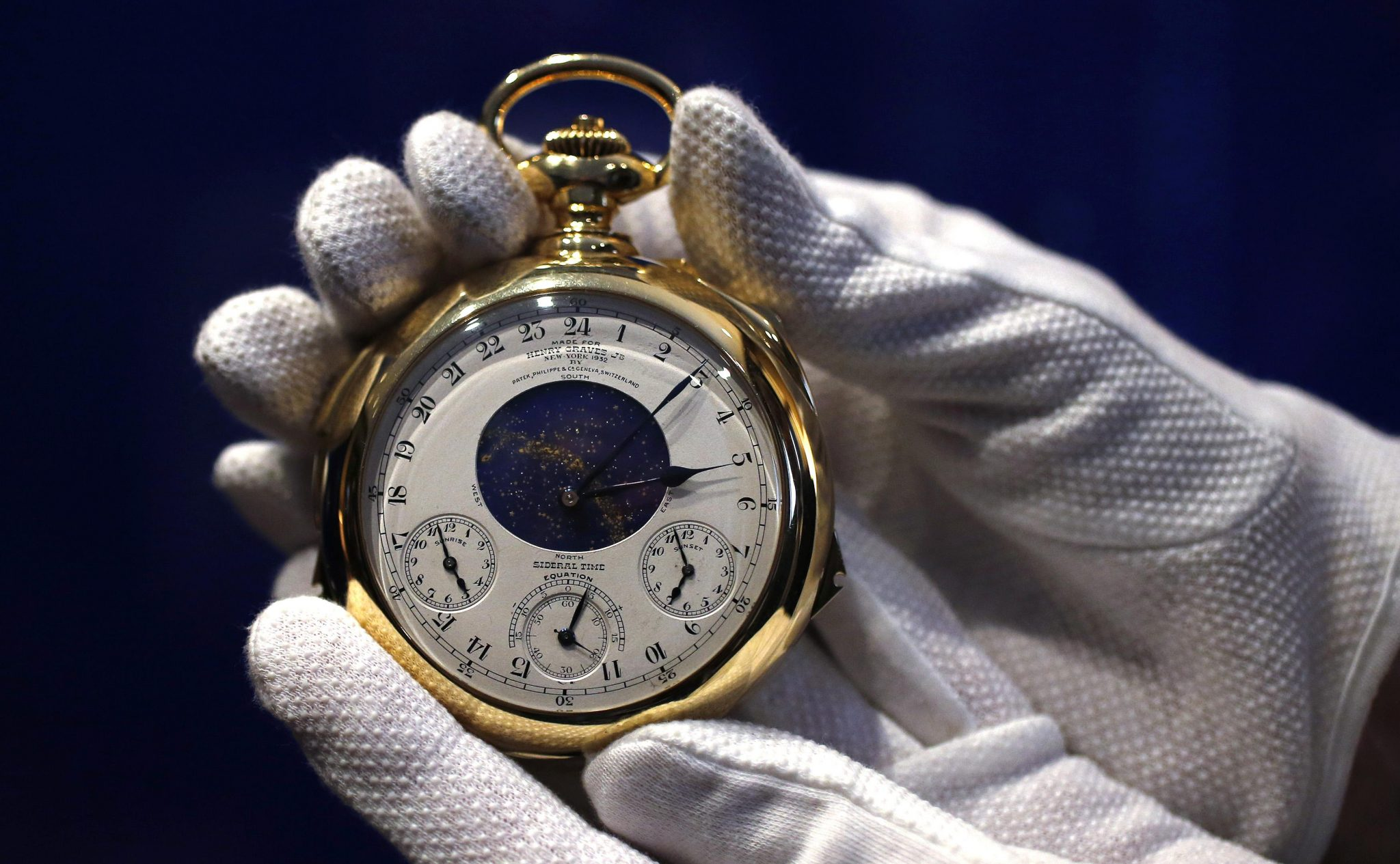 "A staff member holds ""The Henry Graves Supercomplication"" handmade watch by Patek Philippe which was completed in 1932 at Sotheby's auction house in London"