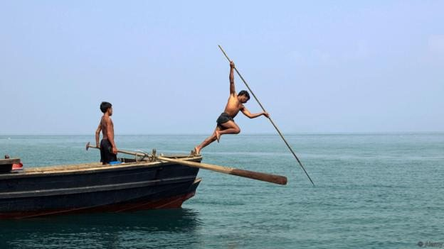 BJG3JB Myanmar sea-gypsies, the nomadic hunter-gatherers of South East Asia harpooning in the traditional way, leaping off a boat.. Image shot 2007. Exact date unknown.