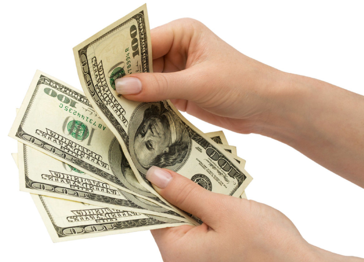 FI-MAYERS14 The falling dollar has made buying U.S. greenbacks even more expensive US Dollars in woman's hand, over white, isolated with clipping path Uploaded by: mayers, adam